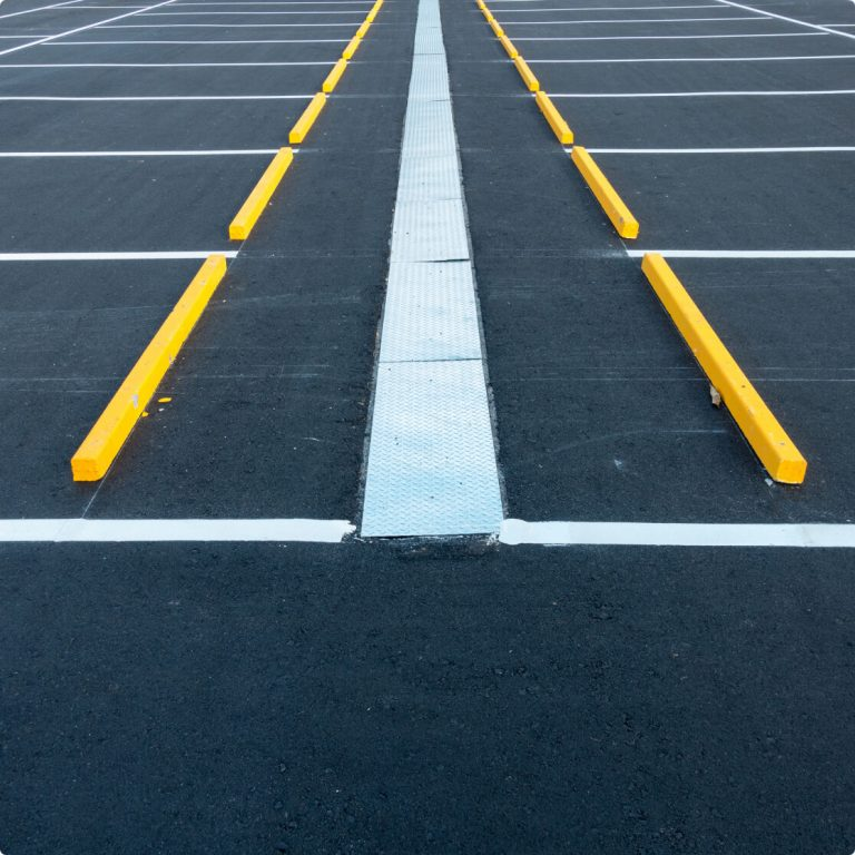 yellow wheel stops with white stripes on pavement