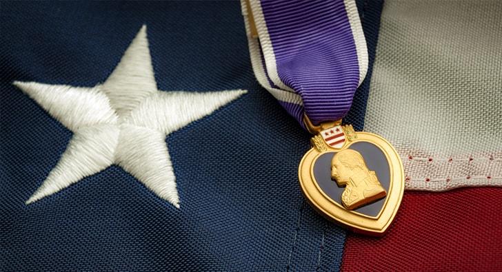 purple heart laying on american flag